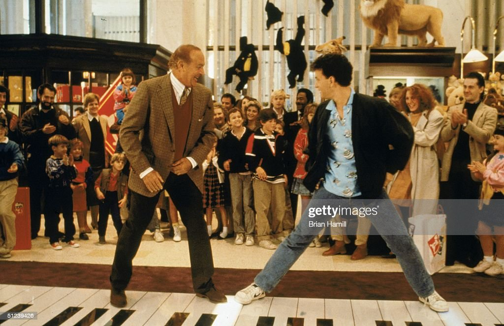 1988, American actors Robert Loggia, left, and Tom Hanks stand on a giant piano keyboard at the FAO Schwartz toy store in a still from the film 'Big' directed by Penny Marshall.