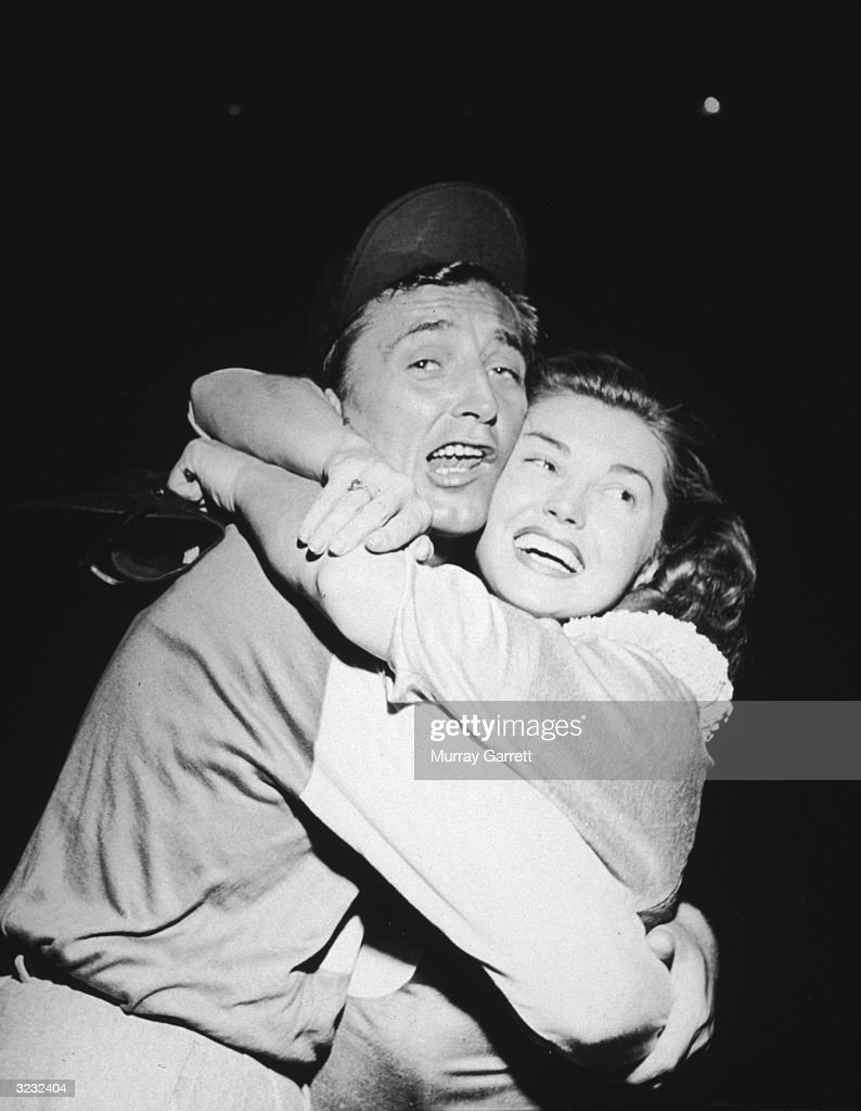 American actors <a gi-track='captionPersonalityLinkClicked' href=/galleries/search?phrase=Robert+Mitchum&family=editorial&specificpeople=206827 ng-click='$event.stopPropagation()'>Robert Mitchum</a> (1917 - 1997) and <a gi-track='captionPersonalityLinkClicked' href=/galleries/search?phrase=Esther+Williams&family=editorial&specificpeople=123838 ng-click='$event.stopPropagation()'>Esther Williams</a> embrace at the 'Out of This World' Series charity baseball game, Los Angeles, California. Mitchum, wearing a baseball uniform, makes a face.