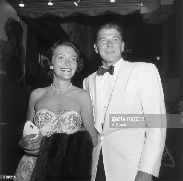 American actors Ronald Reagan and Nancy Davis standing together and smiling while at the premiere of director Elia Kazan's film 'A Streetcar Named...