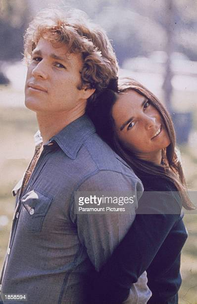 American actors Ryan O'Neal and Ali MacGraw stand back to back outdoors in a still from the film 'Love Story' directed by Arthur Hiller 1970