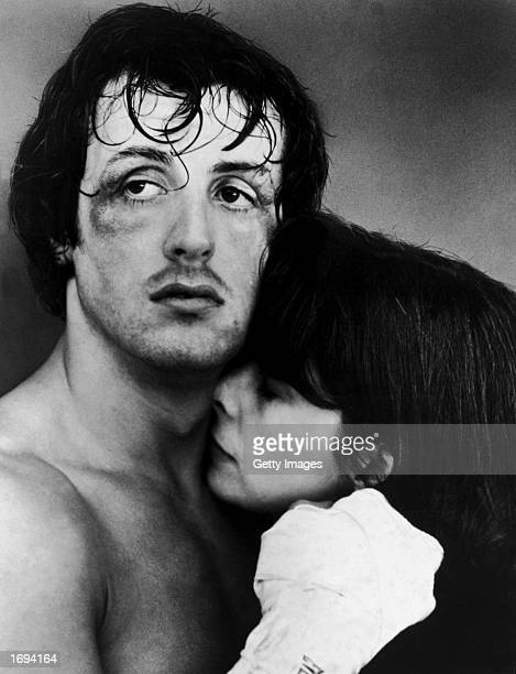 American actors Sylvester Stallone and Talia Shire embrace in a headshot still from the film 'Rocky' directed by John G Avildsen 1976 Stallone's face...