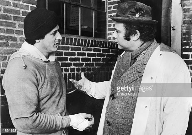 American actors Sylvester Stallone wearing training clothes and Burt Young talk outdoors in a still from the film 'Rocky' directed by John G Avildsen...