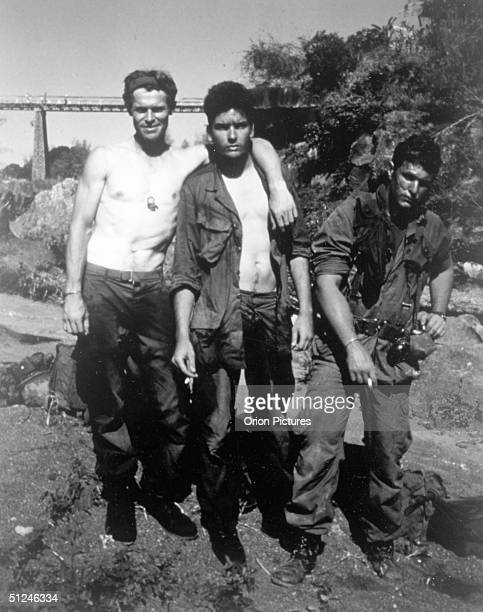 1986 American actors Willem Dafoe Charlie Sheen and Tom Berenger pose outdoors on the set of director Oliver Stone's film 'Platoon'