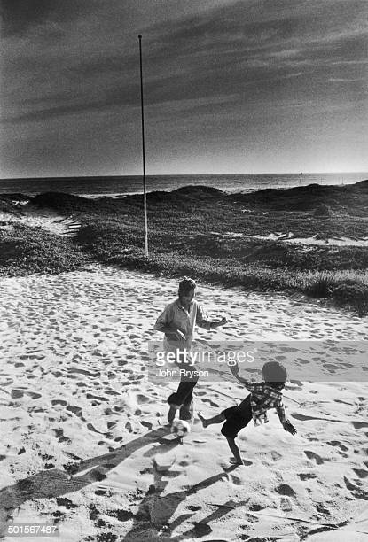 American actress Ali MacGraw and her son Josh Evans play together on the beach California 1978