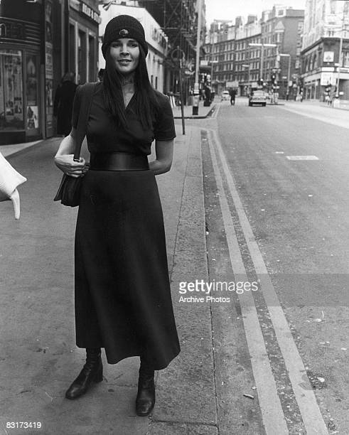 American actress Ali MacGraw stands on a street corner wearing a dark dress and a knitted hat London England 8th March 1971
