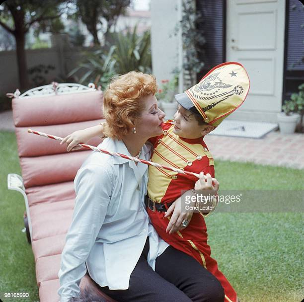American actress and comedienne Lucille Ball kisses her son Desi Arnaz Jr who is dressed as a drum major with a baton in the back yard of their home...