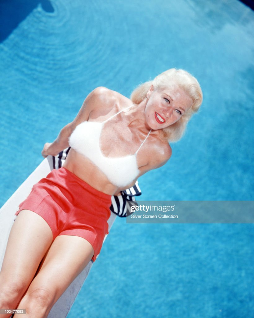 American actress and dancer <a gi-track='captionPersonalityLinkClicked' href=/galleries/search?phrase=Ginger+Rogers&family=editorial&specificpeople=93466 ng-click='$event.stopPropagation()'>Ginger Rogers</a> (1911 - 1995) sitting on a diving board in red shorts and a furry white bra top, circa 1955.