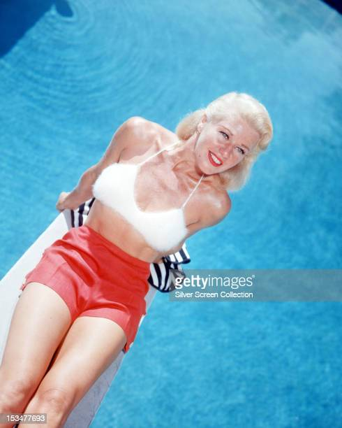 American actress and dancer Ginger Rogers sitting on a diving board in red shorts and a furry white bra top circa 1955