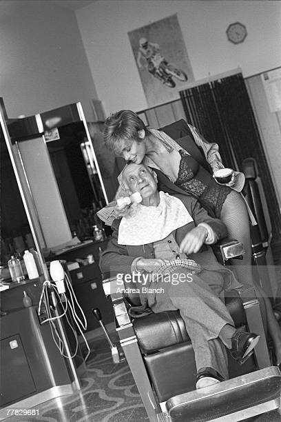 American actress and model Lauren Hutton dressed in an open shirt and sleeveless jacket semitransparent lace teddy and fishnet stockings uses a brush...