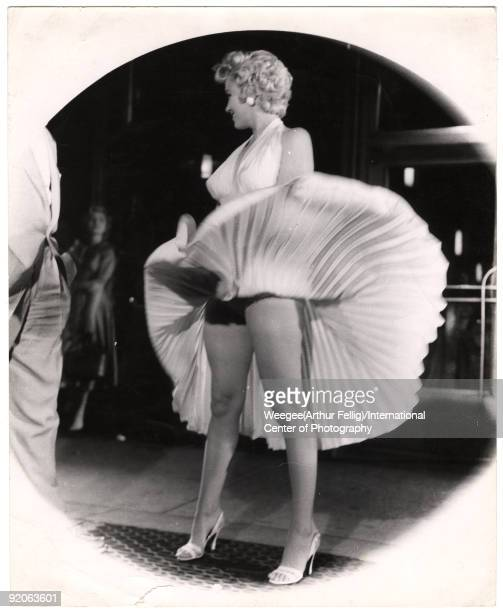 American actress and sex symbol Marilyn Monroe stands on a subway grate as her skirt billows out around her on location during the filming of 'The...