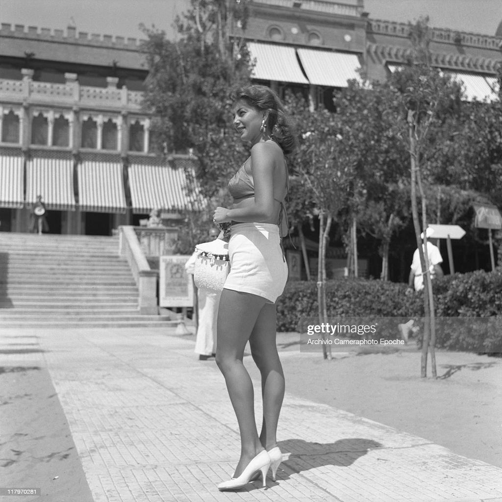American actress and singer Abbe Lane wearing a swimming bra and a highwaisted hot pants holding a handbag standing on the path of the Excelsior...