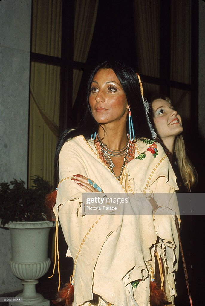 American actress and singer Cher wears beaded jewelry as she stands with arms folded in a Native American Poncho alongside her halfsister actress...