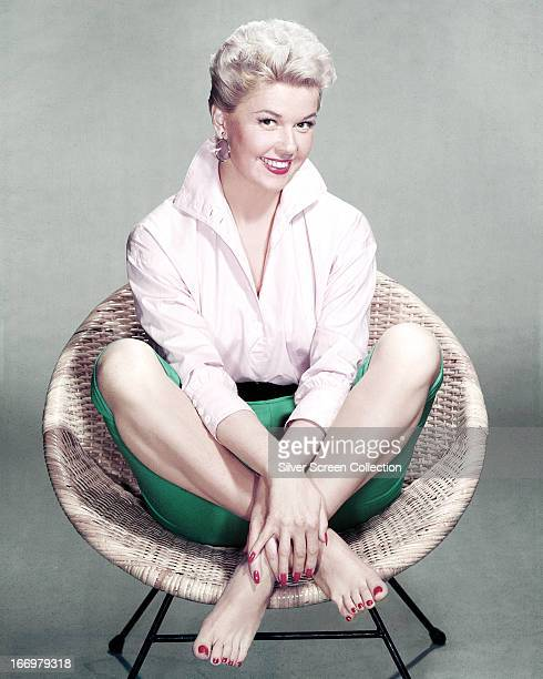 American actress and singer Doris Day sits crosslegged and barefoot in a rattan chair circa 1955