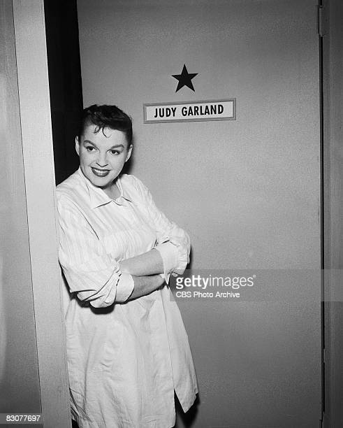 American actress and singer Judy Garland stands outside her dressing room door backstage on the set of the live performance anthology series 'Ford...