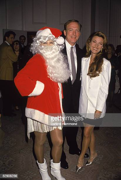 American actress Angie Dickinson wears a Santa Claus costume as she poses with American actor James Keach and British actress Jane Seymour at an...