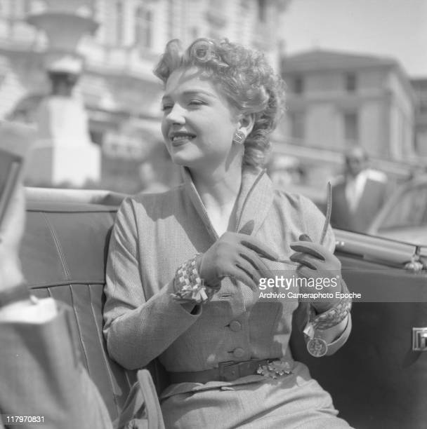 American actress Anne Baxter wearing a tailleur a belt and gloves holding sunglasses and looking around while sitting in a car Cannes 1953