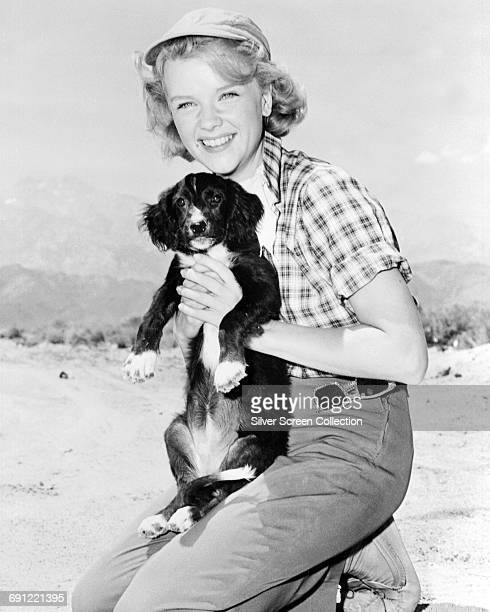 American actress Anne Francis holding a small dog circa 1950