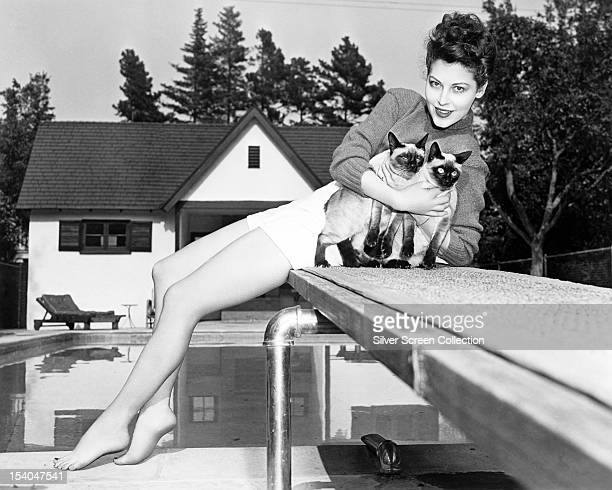 American actress Ava Gardner sitting on a diving board and holding a pair of siamese cats circa 1945