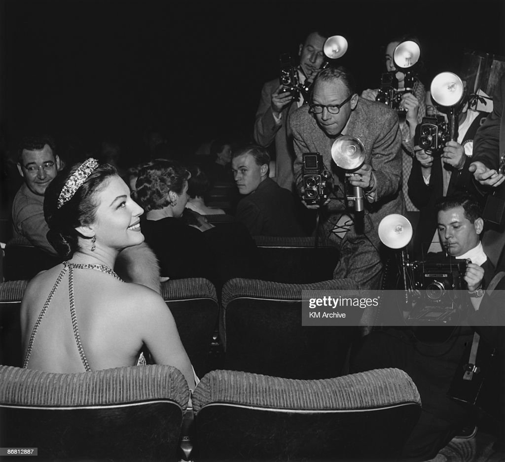 American actress Ava Gardner (1922 - 1990) smiles for photographers, while sitting in a theater for the premiere of director Joseph L Mankiewicz's film, 'The Barefoot Contessa,' in which she starred, September 1954.