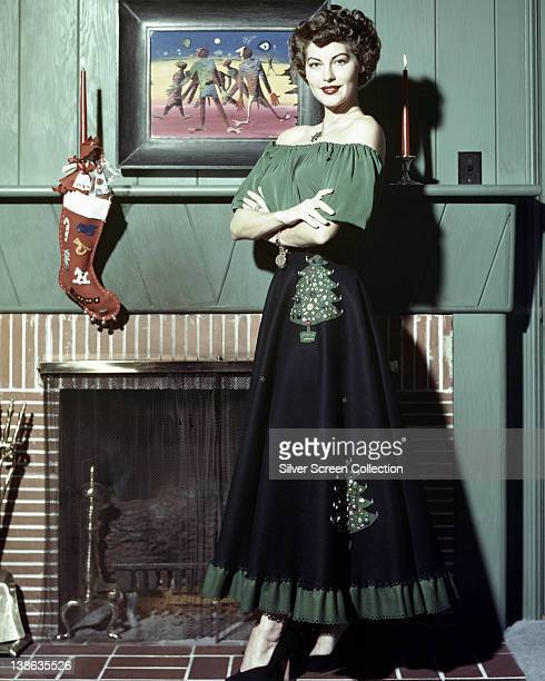 American actress Ava Gardner wearing a green and black dress with Christmas tree motifs on the skirt posing beside a fireplace on which hangs a...