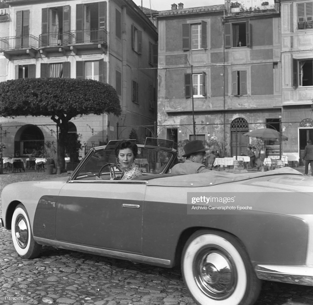 American actress Ava Gardner wearing a polkadotted dress and gloves sitting in a car with actor Humphrey Bogart Portofino 1954