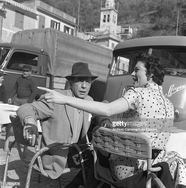 American actress Ava Gardner with Humphrey Bogart sitting in front of some vans in Portofino she is wearing a polkadotted dress 1954