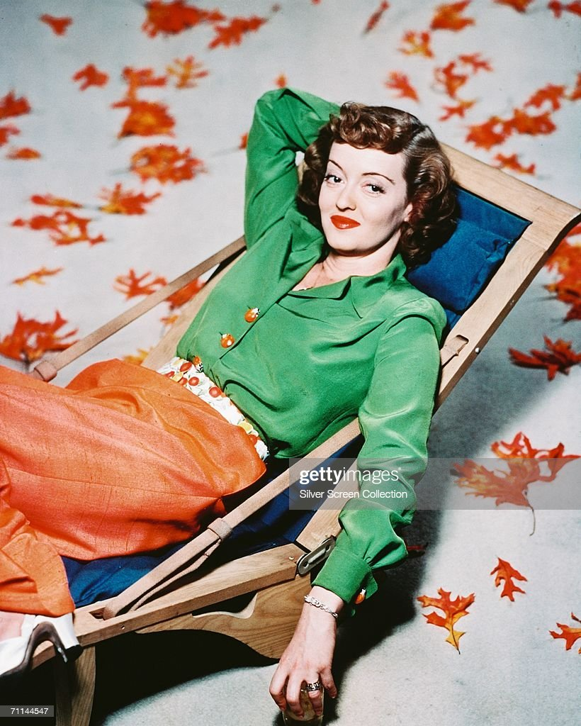 American actress <a gi-track='captionPersonalityLinkClicked' href=/galleries/search?phrase=Bette+Davis+-+Actress&family=editorial&specificpeople=93133 ng-click='$event.stopPropagation()'>Bette Davis</a> (1908 - 1989), relaxing in a deckchair surrounded by autumn leaves, circa 1940.