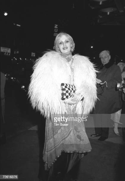 American actress Candy Darling born James Lawrence Slattery pauses for a picture outside of a theater as a man looks on Broadway New York early 1970s
