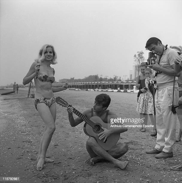 American actress Carroll Baker wearing a fancy bikini dancing on the seashore next to Italian singer Tony Renis playing spanish guitar sat on the...