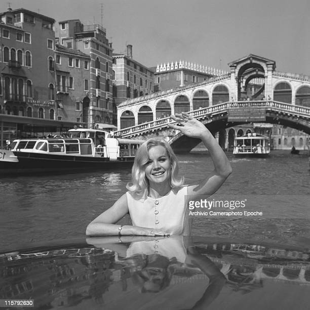 American actress Carroll Baker wearing a white dress portrayed on a water taxi on the Canal Grande Rialto Bridge in the background Venice 1960s
