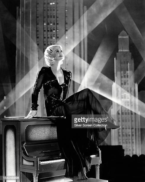 American actress dancer and singer Ginger Rogers sitting on an upright piano with a backdrop of a cityscape at night circa 1935