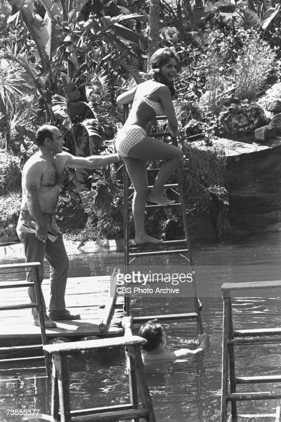 American actress Dawn Wells in character as Mary Ann wears a bikini swimsuit as she climbs a ladder above an artifical lagoon with the assistance of...