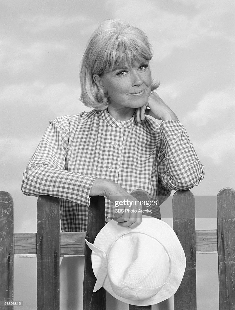 American actress Doris Day holds her hat and leans against a picket fence chin in hand in a formal portrait as Doris Martin her character on 'The...