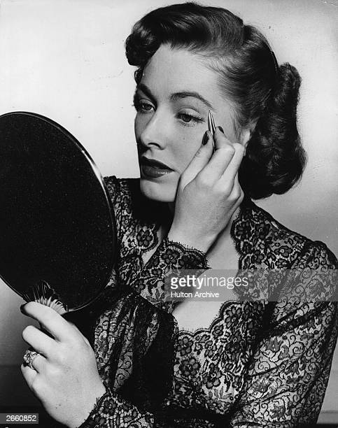 American actress Eleanor Parker plucks her eyebrows as part of her beauty routine for the film 'Chain Lightning' directed by Stuart Heisler for...