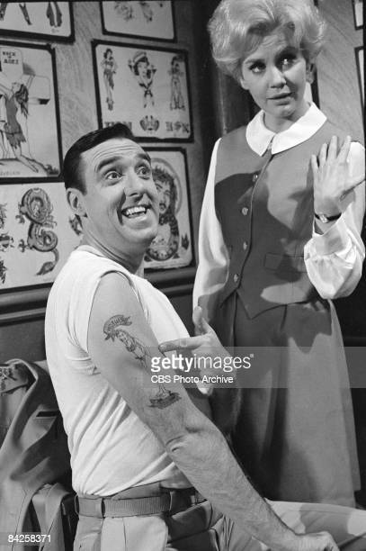 American actress Elizabeth MacRae stands nearby and actor Jim Nabors shows off his character's new tattoo in an episode of the television comedy...
