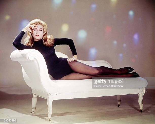 American actress Elizabeth Montgomery wearing in a black leotard and reclining on a chaise longue circa 1967