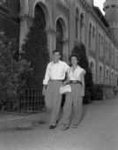 American actress Elizabeth Taylor wearing a sleeveless shirt and wide trousers holding a handbag walking next to her first husband Conrad 'Nicky'...