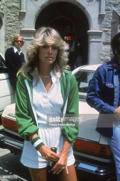 American actress Farrah Fawcett poses with a tennis racket outside the Playboy Mansion where she participated in a charity tennis match Los Angeles...