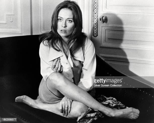 American actress Faye Dunaway sitting crosslegged on a chaise longue and smoking a cigarette circa 1970