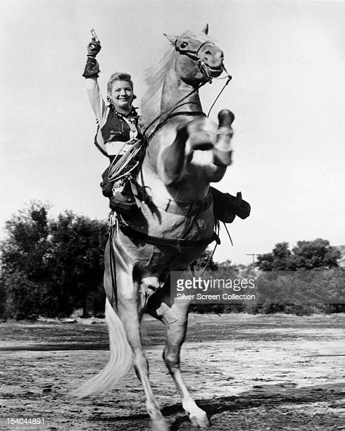 American actress Gail Davis firing a pistol from the back of a rearing horse in the title role of the American TV western series 'Annie Oakley' circa...