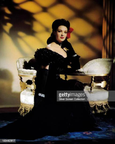 American actress Gene Tierney sitting on a love seat in a black evening gown and evening gloves circa 1945