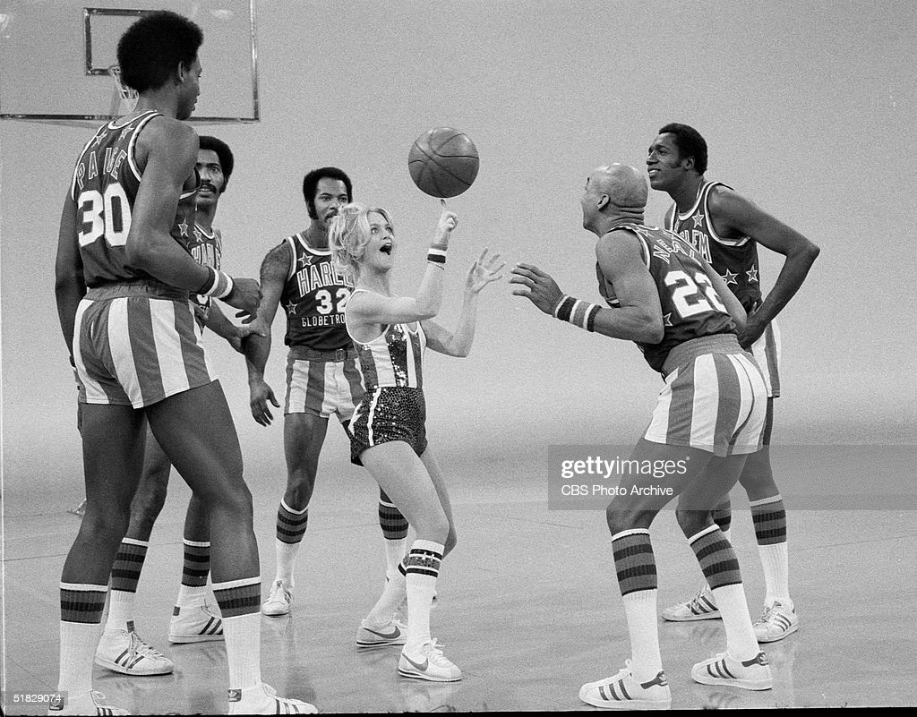 American actress Goldie Hawn spins a basketball on her finger while performing with the Harlem Globetrotters, including Robert Paige (#30), Curley Neal (#22), and Meadowlark Lemon (R), during the CBS program 'The Goldie Hawn Special,' January 25, 1978.