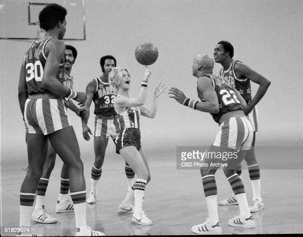 American actress Goldie Hawn spins a basketball on her finger while performing with the Harlem Globetrotters including Robert Paige Curley Neal and...