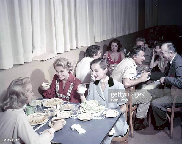 American actress Grace Kelly eating with friends in a canteen circa 1954 Actors Elizabeth Taylor and Stewart Granger are at the table behind them In...