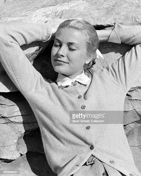 American actress Grace Kelly wearing a cardigan and reclining with her eyes shut against a rock face circa 1955