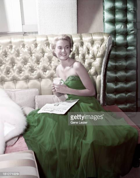 American actress Grace Kelly wearing a green dress for St Patrick's Day 1954 She is reading a copy of MGM's Studio News