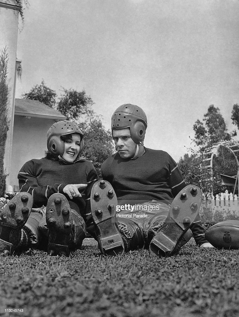 American actress Gracie Allen and her husband actor George Burns wearing football uniforms in September 1938