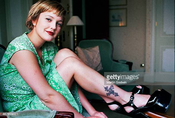 American actress in a green dress and black patent platforms with a tattoo of a cross on her calf photographed in her hotel room in London 25th April...