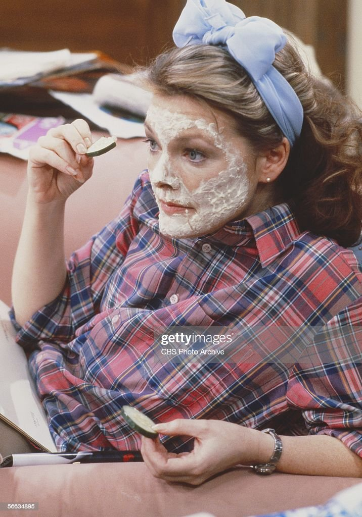 American actress Jane Curtain wears a facial mask as she sits on a couch and holds cucumber slices in a still from the CBS television sitcom 'Kate...