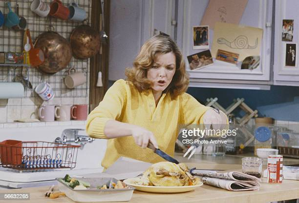 American actress Jane Curtin struggles with dinner in the kitchen in a scene from the television sitcom 'Kate Allie' New York New York 1985